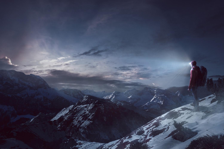 Wanderer mit Stirnlampe auf einem Berg